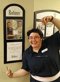 Picture of woman smiling and pointing to plaque on the wall that says Radiance