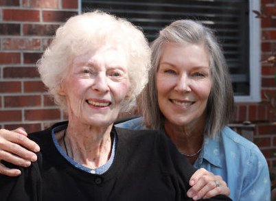 Picture of two women smiling, one has hands on shoulder of other