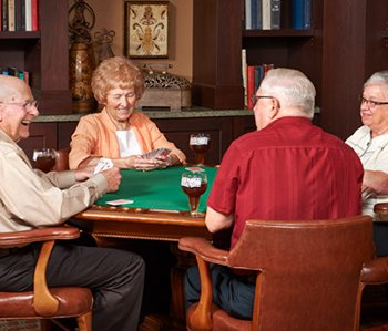 Picture of a group of people playing cards laughing