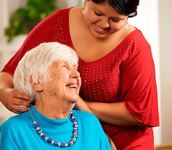 Young woman combing older ladies hair