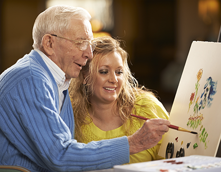 Senior man painting with young girl