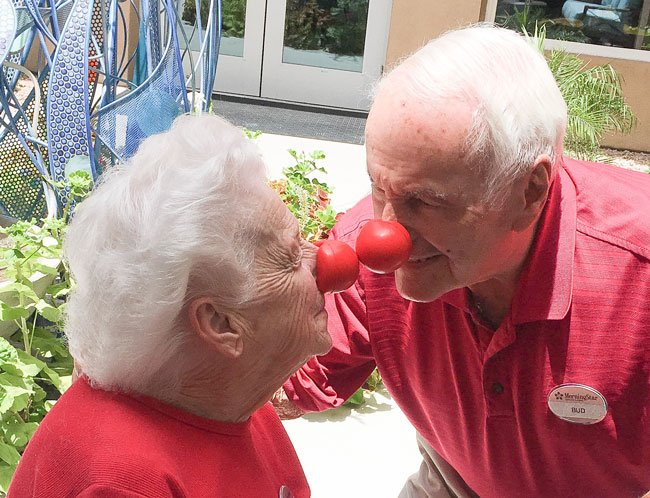 Picture of a man and a woman with clown noses on touching noses